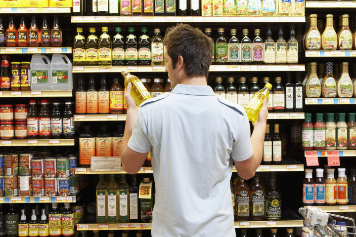 Young man in supermarket comparing bottles of oil, rear view, close-up